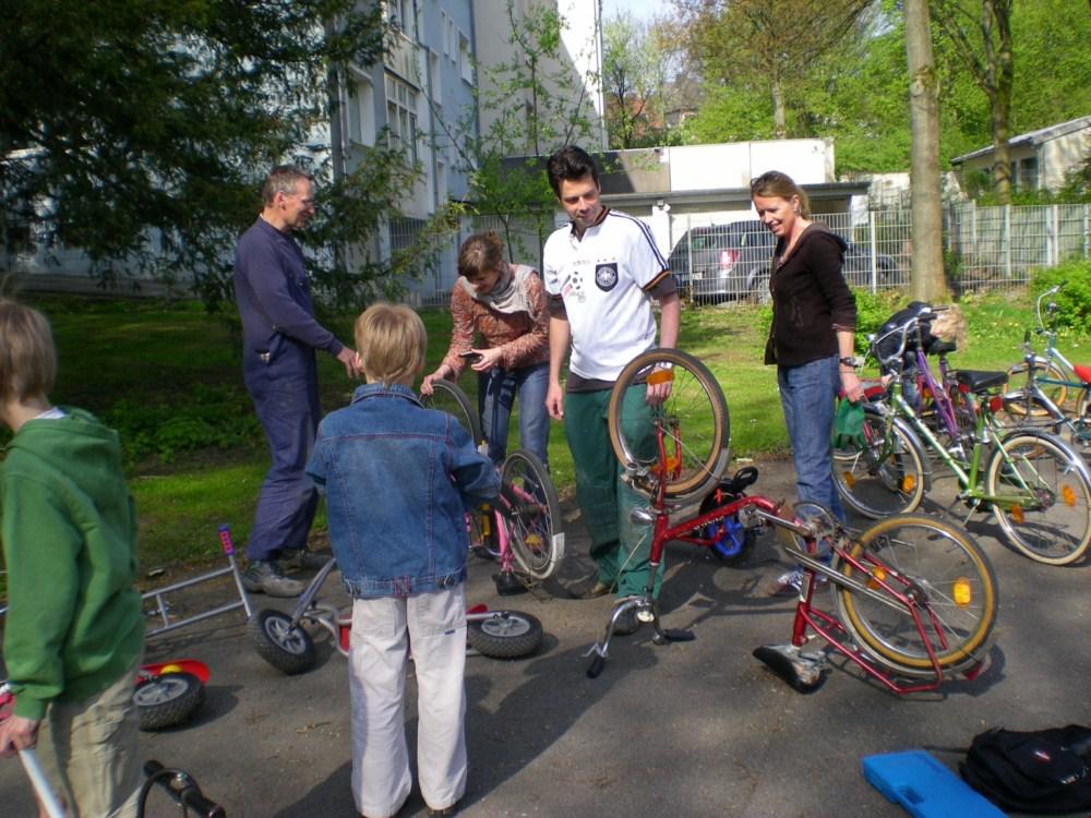 Kinder,  Eltern und Lehrerinnen reparieren die Fahrräder