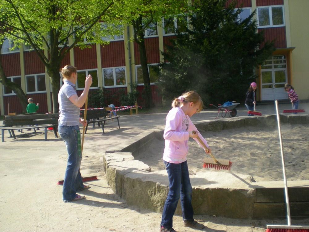 Kinder,  Eltern und Lehrerinnen fegen,  säubern und bemalen den Schulhof