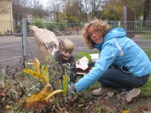 Eltern und Kinder arbeiten im Schulgarten
