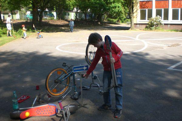 Kinder und Eltern bei der Gartenarbeit auf dem Schulhof