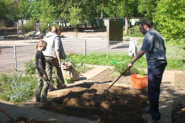 Kinder und Eltern im Schulgarten