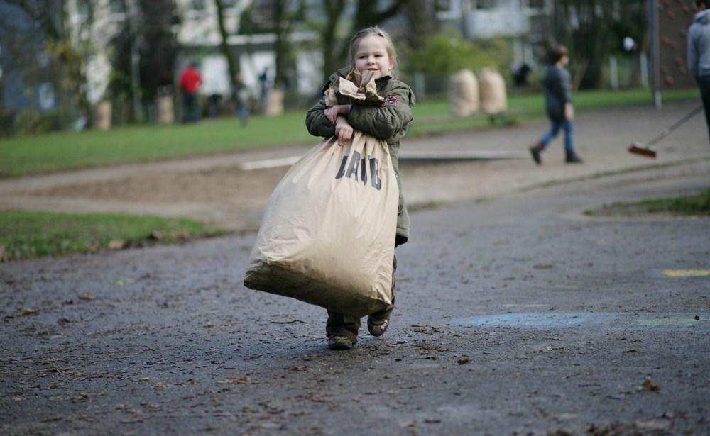 Kinder und Eltern fegen Laub