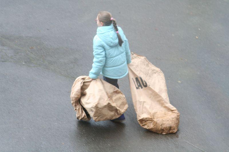 Kind mit Laubsäcken