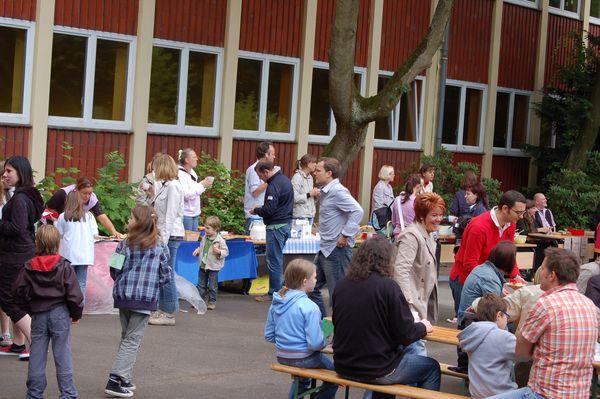 Eltern und Kinder verschnaufen bei Kaffee,  Kuchen,  Salat und Grillwurst