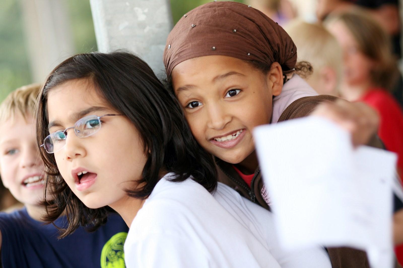 Kinder zeigen Begeisterung und feuern die anderen Kinder an