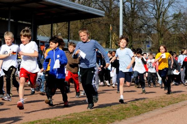 Kinder laufen auf dem Sportplatz