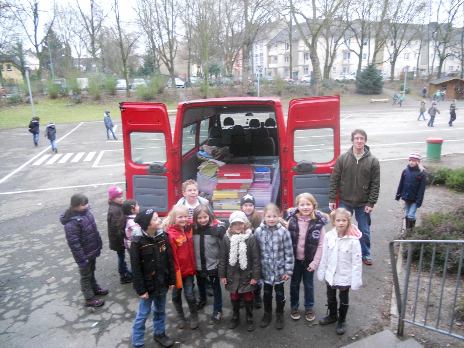 Kinder beladen ein Auto mit den Spenden für das Friedensdorf