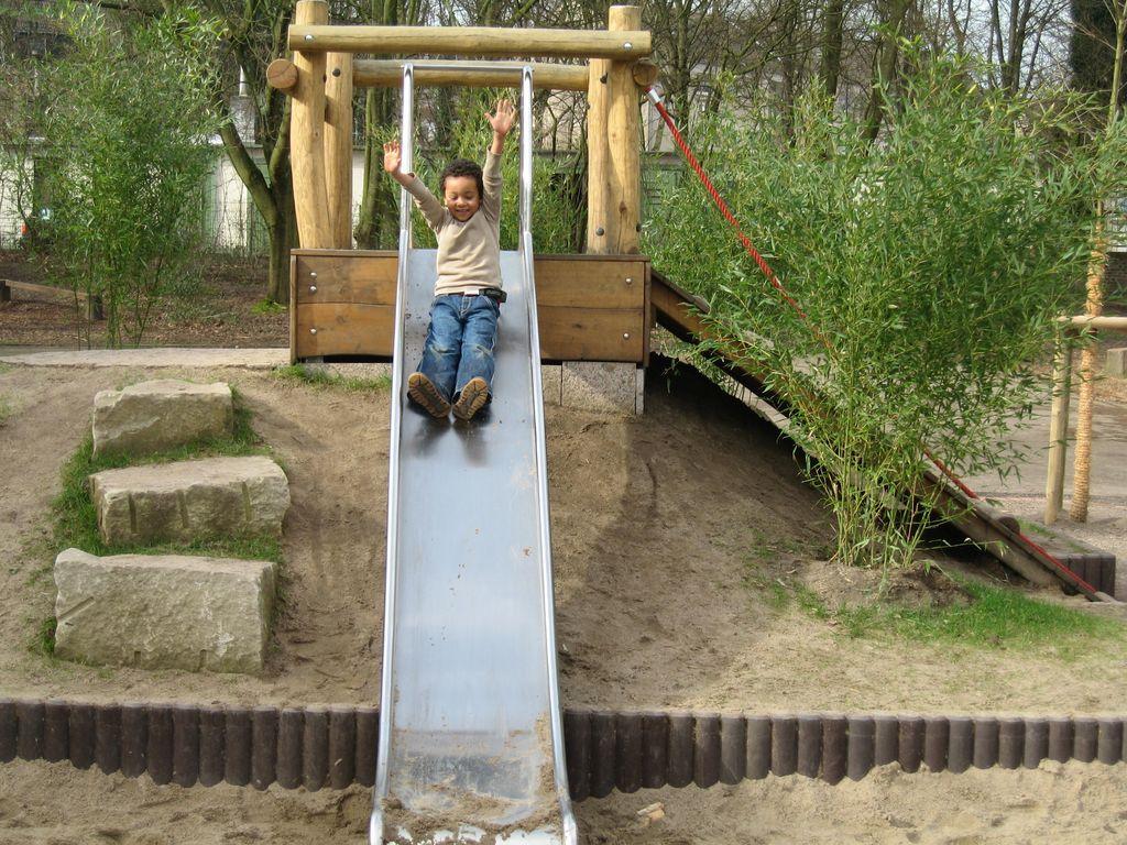 Kind rutscht eine Rutsche hinunter
