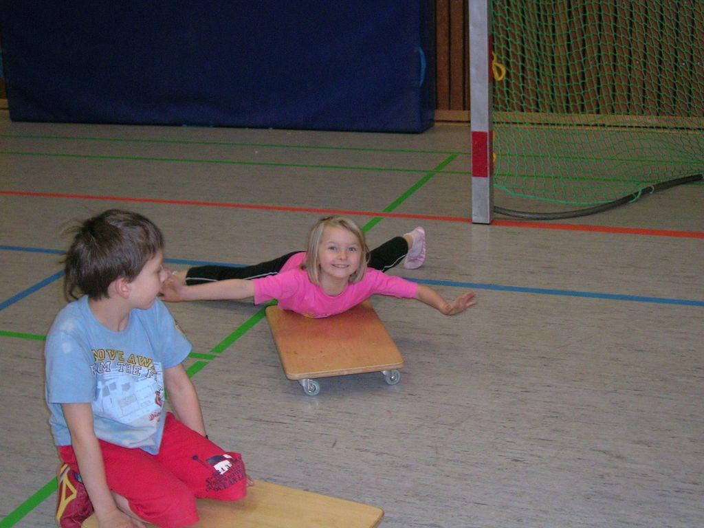 Kinder rollen auf Rollbettern