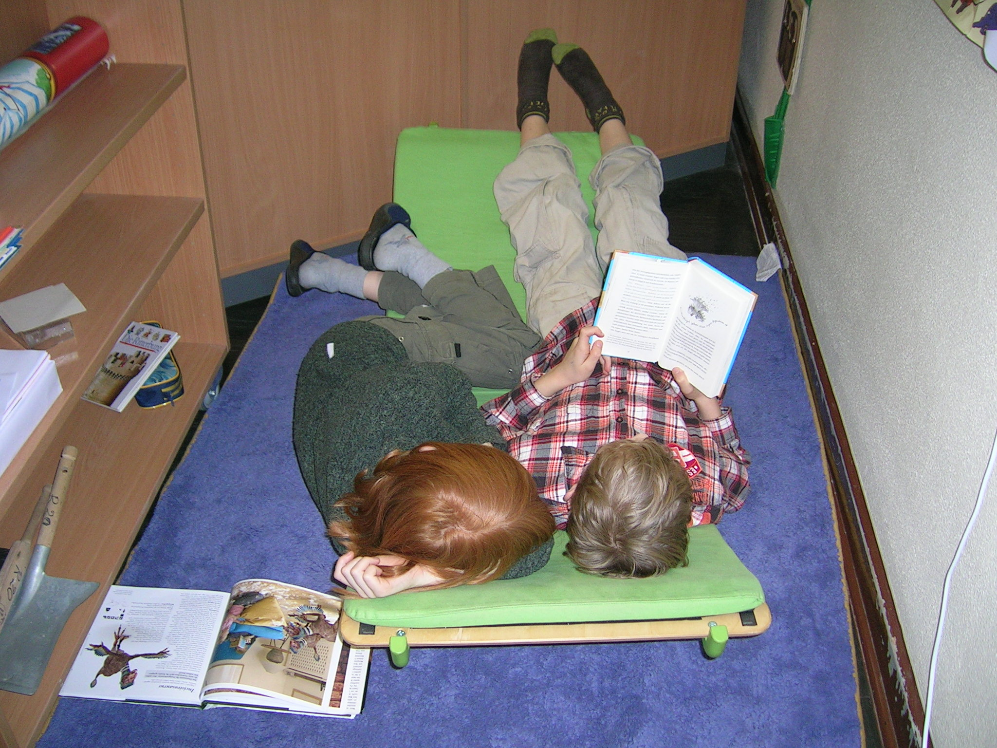 Kinder lesen entspannt auf einer Wippe